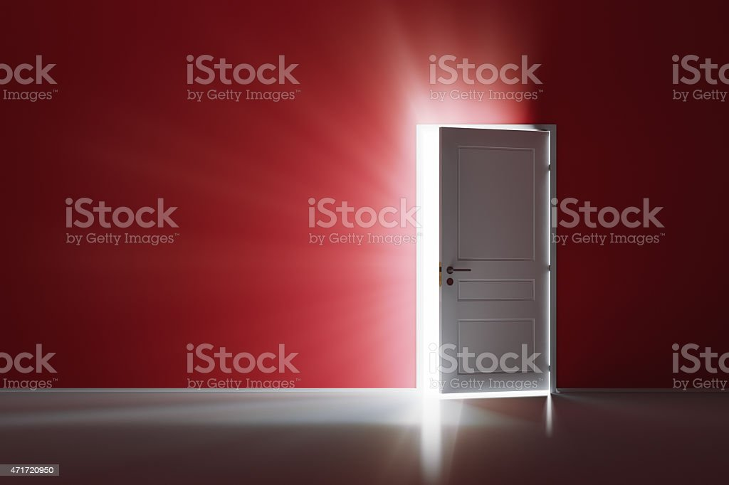 Open white door on red wall stock photo