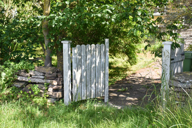 Open white gate into a garden stock photo