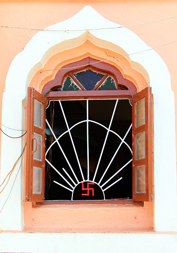 Open window of jain temple with ancient symbol of divinity and spirituality on it, India