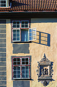 Open window with a shadow on the facade of an old house with a medieval bas-relief