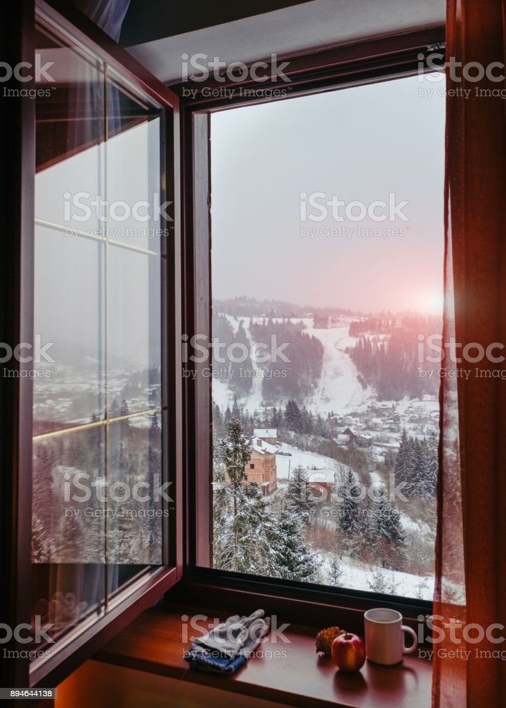 Open window overlooking sunrise at winter Carpathian Slavske village stock photo
