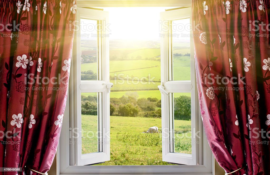Open window with countryside view and sunlight streaming in stock photo