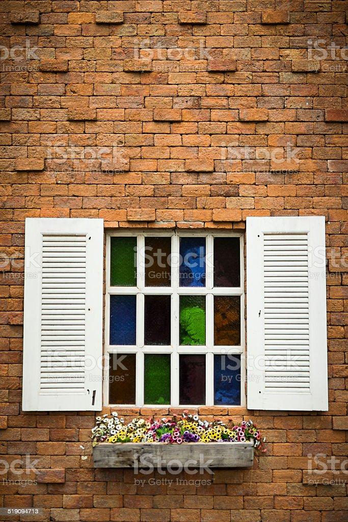 Open Window With Flower Basket On Brick  Wall stock photo