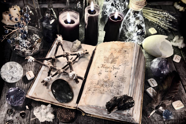 Open witch book with pentagram, black candles, stones, crystals and magic ritual objects stock photo