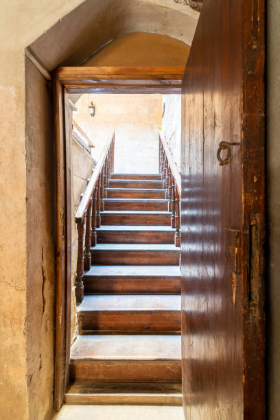 Open wooden door revealing wooden old staircase going up with with reflections of the stairs on the door stock photo