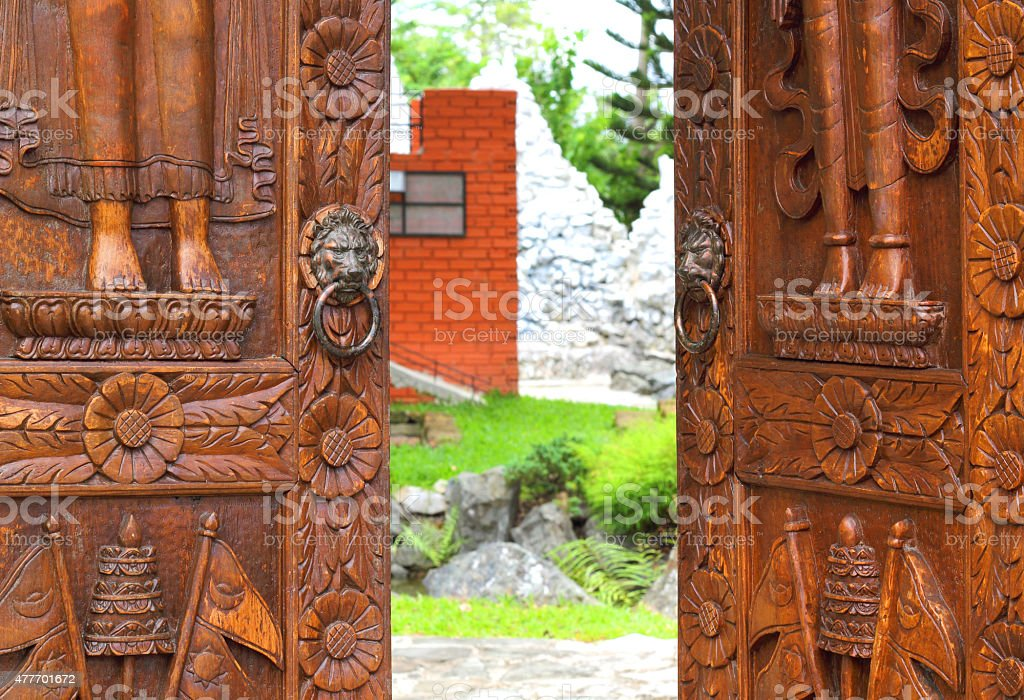 Open wooden door with carved floral patterns stock photo