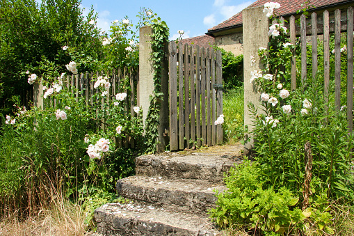 Open wooden garden gate and stone stairs