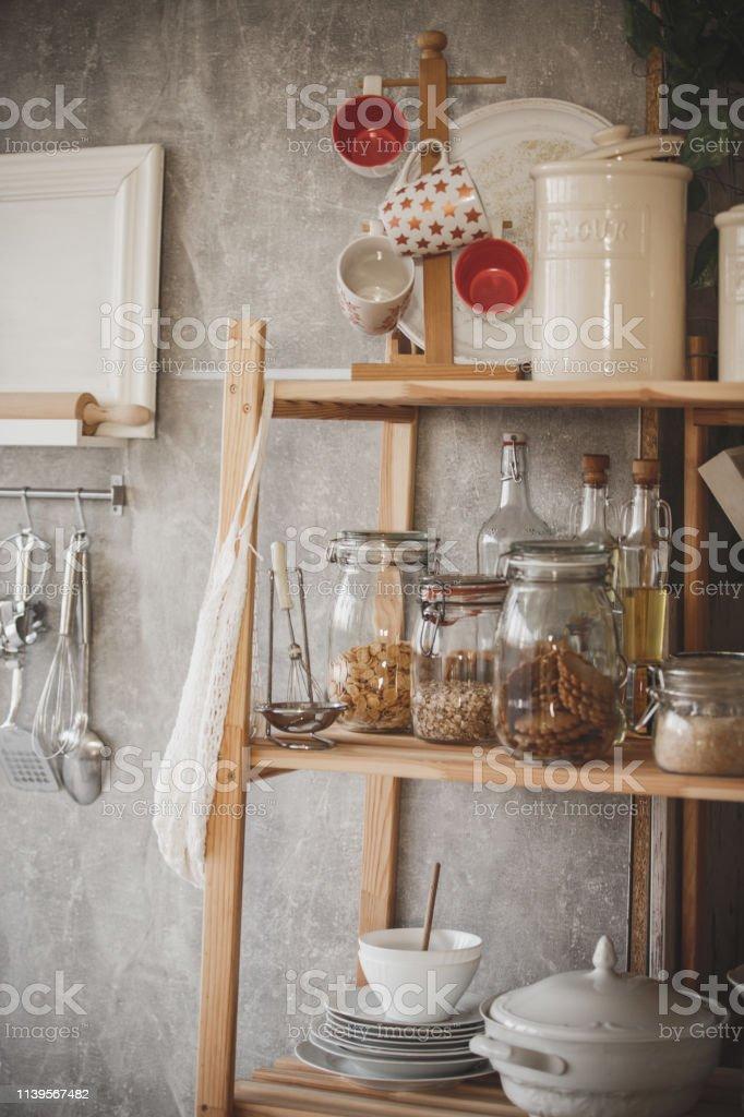 Open wooden kitchen shelves with kitchen utensils.