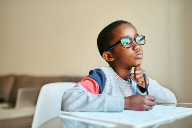 Open your mind to knowledge Shot of an adorable little boy doing his schoolwork at home schoolboy stock pictures, royalty-free photos & images