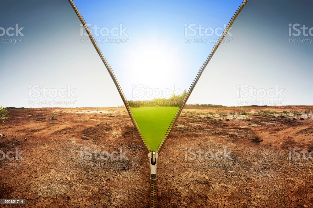 Open zipper showing dry land landscape changing to green land stock photo