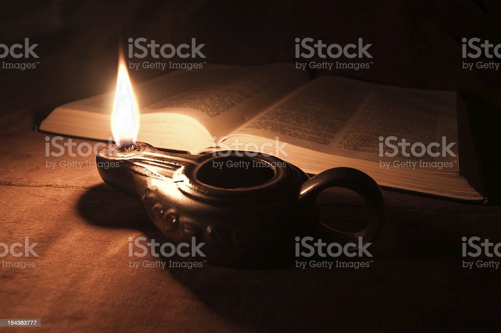 Opened Bible and oil lamp stock photo