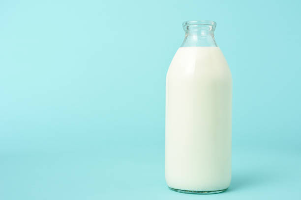 opened blank milk bottle on blue background with copy space - milk bottle stock photos and pictures