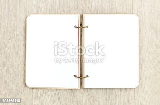 istock Opened blank notepad on wooden table 628366448