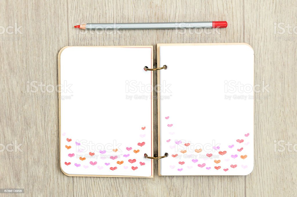 Opened blank notepad with drawn harts on wooden table stock photo