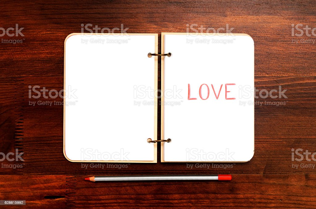 Opened blank notepad with drawn word LOVE on wooden table stock photo