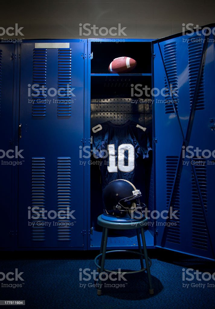 Opened blue locker containing a football and blue jersey stock photo