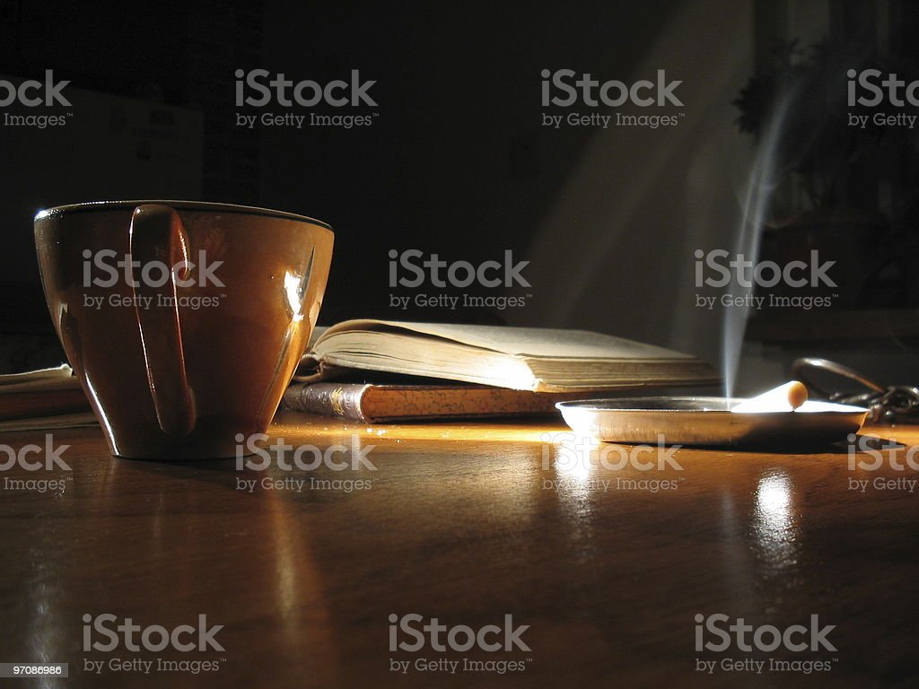 Opened book and cigarette by night. stock photo