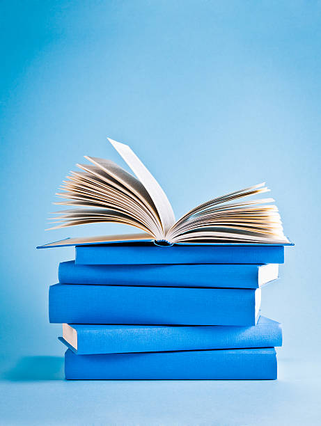 Opened book on top of stack of blue books, knowledge stock photo
