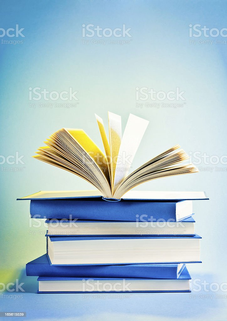 Opened book on top of stack of blue books, wisdom royalty-free stock photo