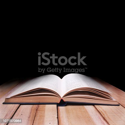 537761721istockphoto Opened Book on Wooden Table Against Black Background 1071570984
