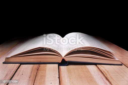 537761721istockphoto Opened Book on Wooden Table Against Black Background 1071571034
