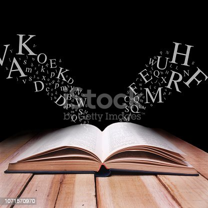 537761721istockphoto Opened Book on Wooden Table Against Black Dark Background with Letters Flying 1071570970