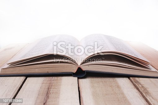 537761721istockphoto Opened Book on Wooden Table Against White Background 1071571344
