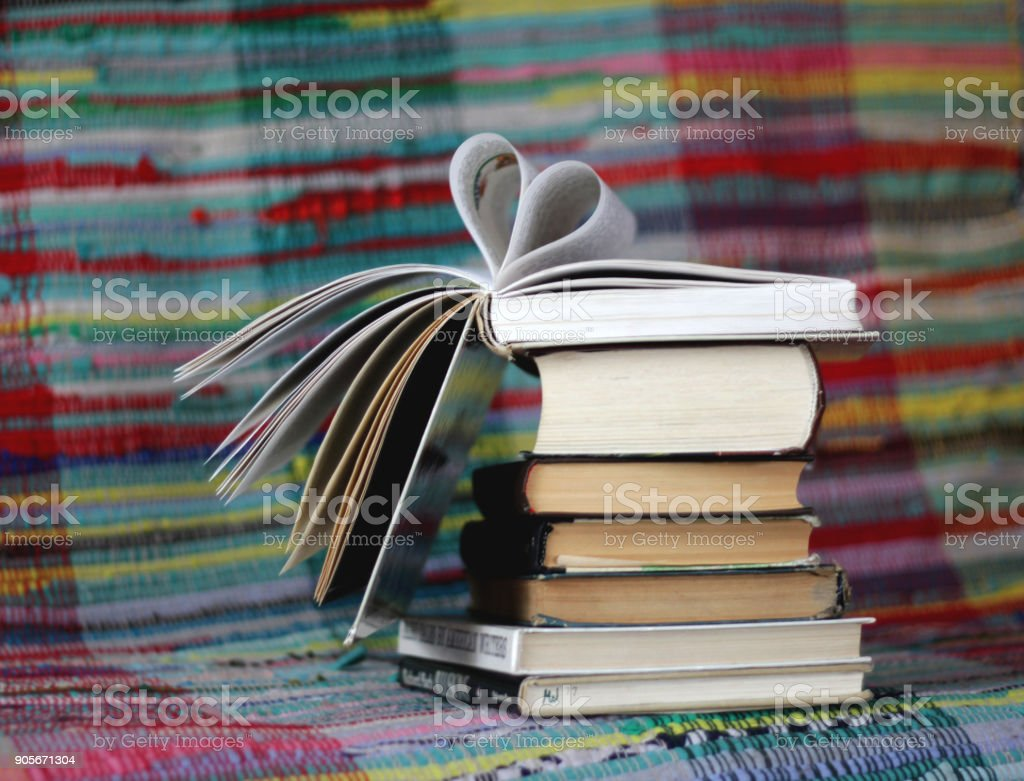 Opened book with heart shaped pages on colourful background stock photo