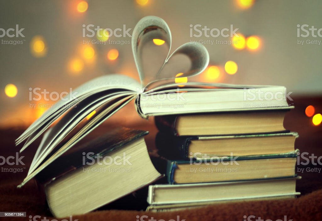 Opened book with heart shaped pages with lights glowing background stock photo