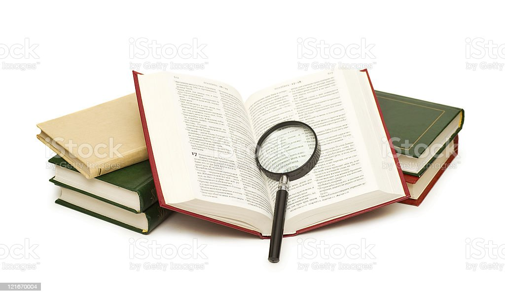 Opened book with magnifying glass stock photo