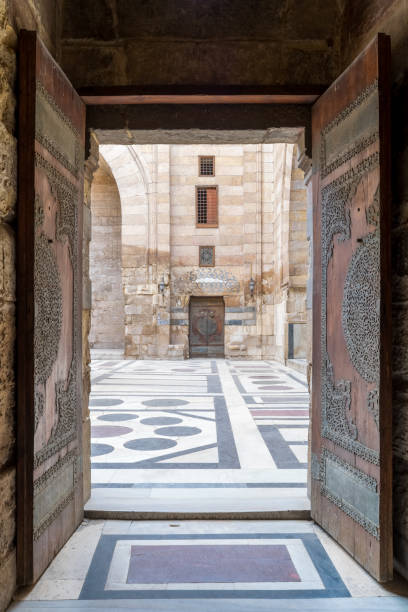 Opened door leading to the courtyard of Al-Sultan Al-Zahir Barquq mosque, Old Cairo, Egypt stock photo