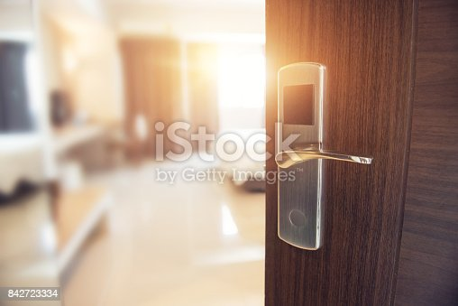 Opened door of hotel room in morning with copy space, sunlight effect.