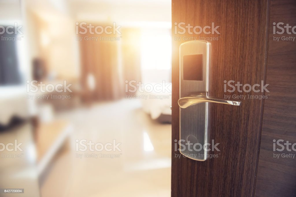 Opened door of hotel room in morning. stock photo