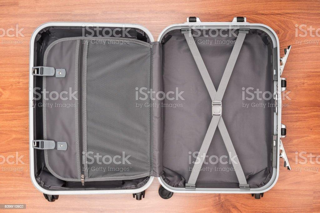 Opened empty travel bag on wooden floor - foto stock