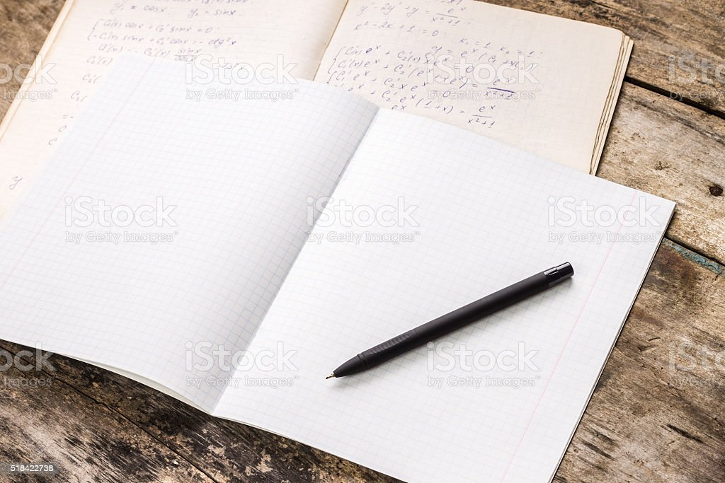 Opened exercise book with workbook of physics stock photo