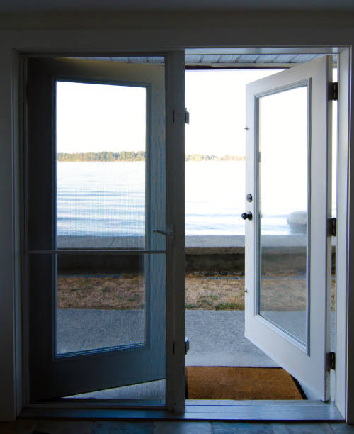 Opened french doors leading to a beach near Saanich Inlet, British Columbia stock photo