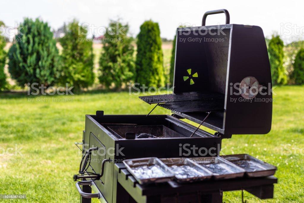 Geöffnete Grill mit Kohle in innen, stehend auf einem Hausgarten im Hintergrund Rasen und Lebensbäume. – Foto