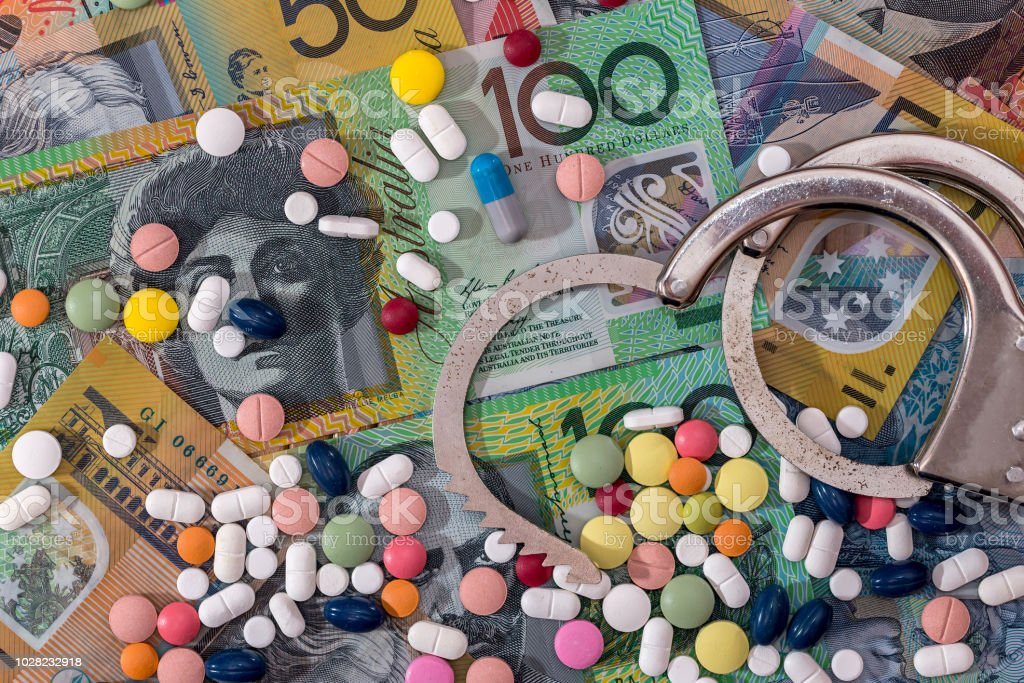 Opened handcuffs with dispersed pills on australian dollar background stock photo