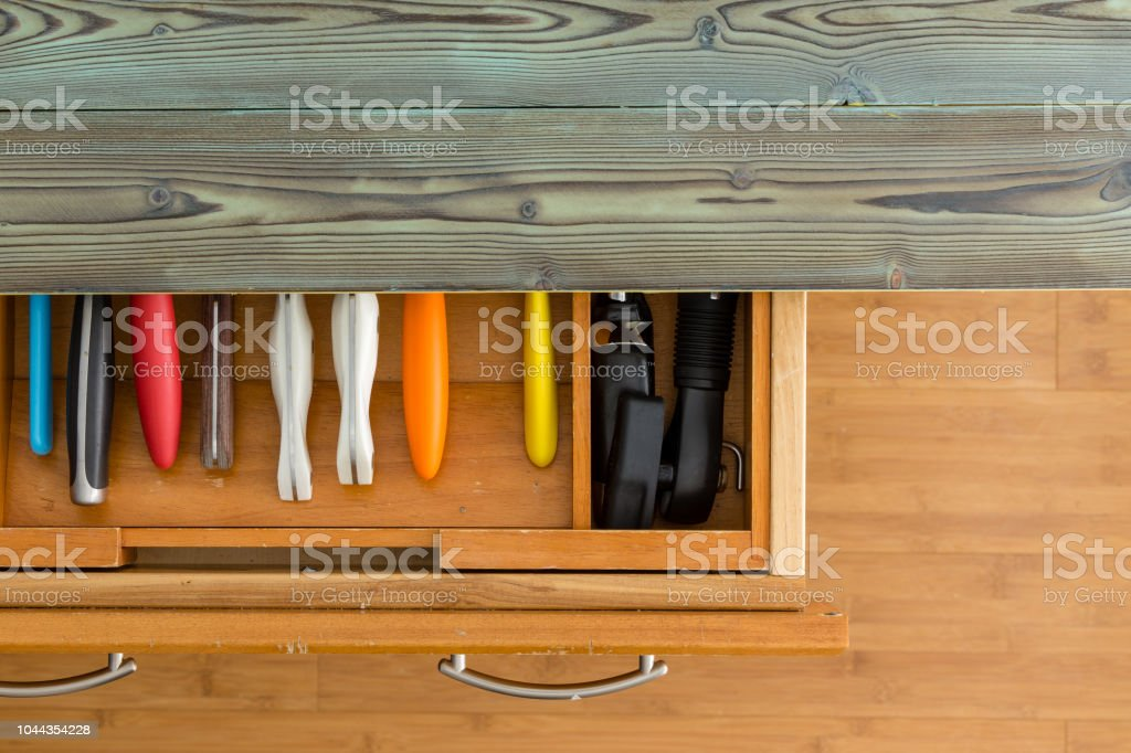 Opened knife drawer showing colorful handles stock photo