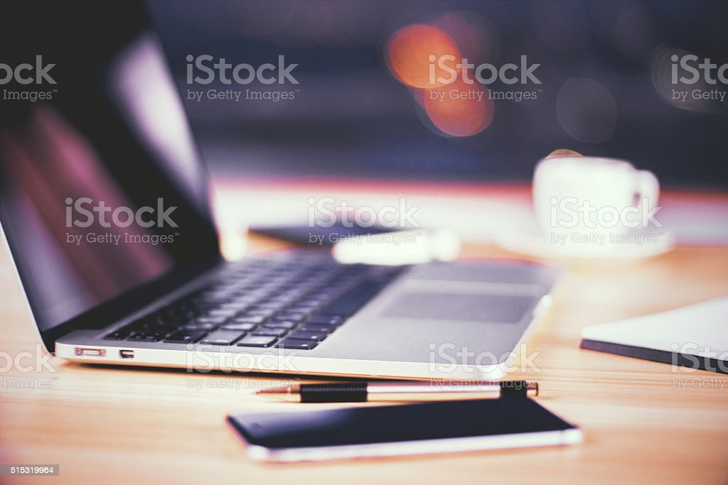 Opened laptop with smartphone, pen and cup of coffee stock photo