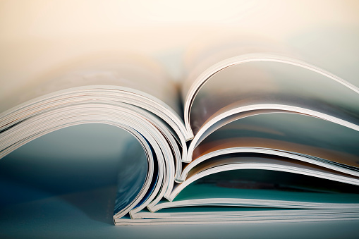 Abstract shot of open magazines stackon table. Macro shot with shallow DOF