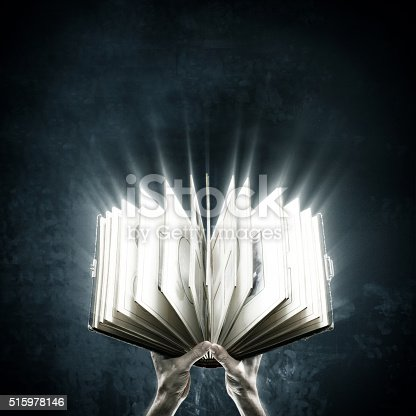 istock Opened magic book with magic lights 515978146