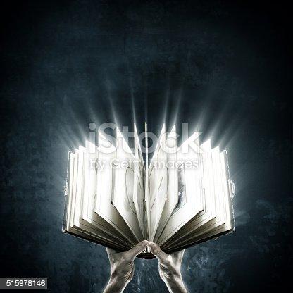 528389419 istock photo Opened magic book with magic lights 515978146