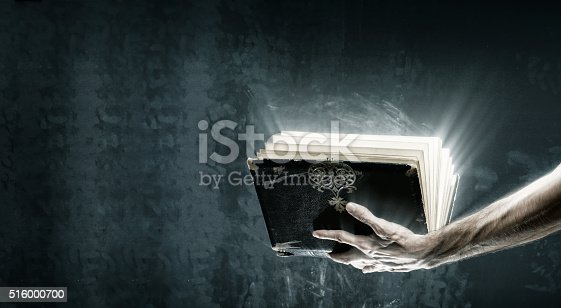 istock Opened magic book with magic lights 516000700