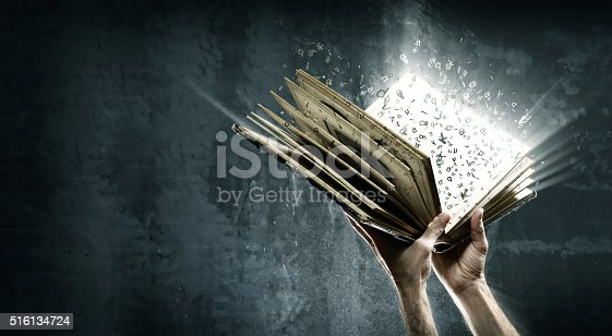 istock Opened magic book with magic lights 516134724