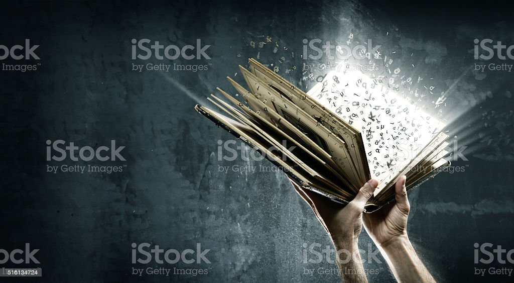 Opened magic book with magic lights stock photo