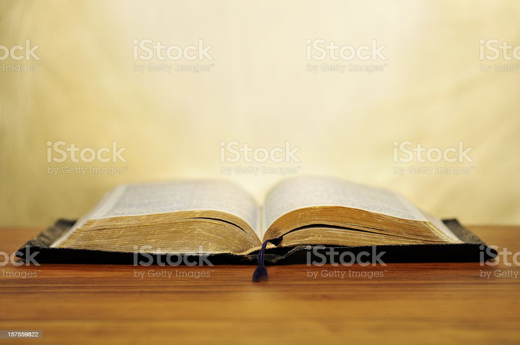 Opened old book on a table with a bookmark stock photo