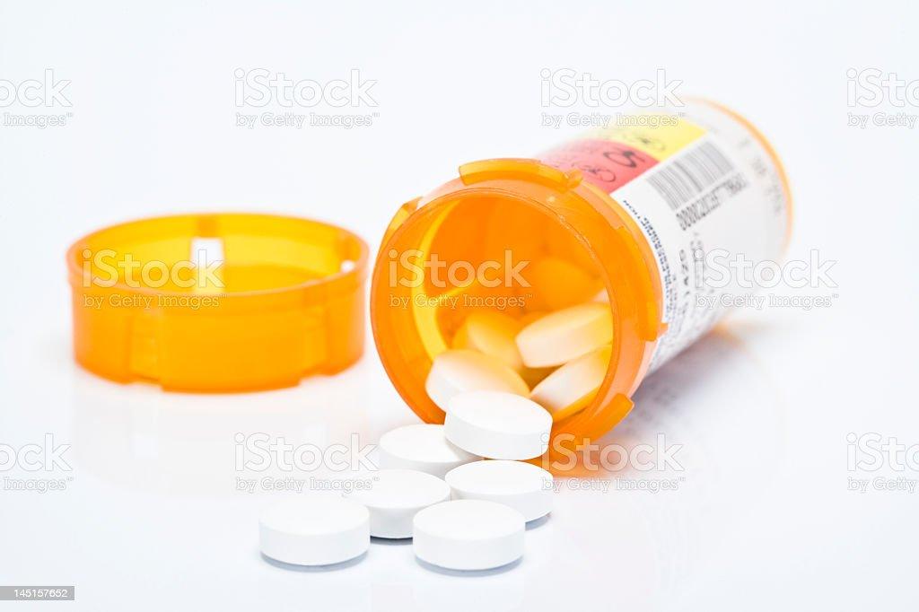 Opened orange bottle of prescription pills stock photo