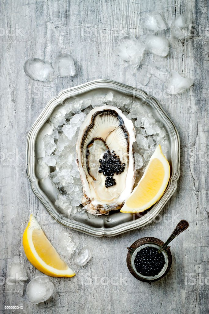 Opened oyster with black sturgeon caviar and lemon on ice in metal plate on grey concrete background. Top view, flat lay, copy space stock photo