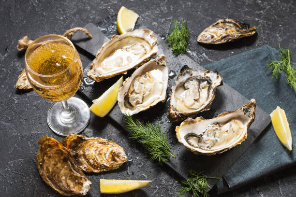 opened oysters and glass of white wine on dark texture background - oyster stock pictures, royalty-free photos & images
